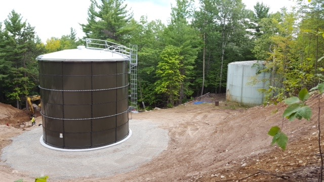 The new tank is in the foreground and the old tank is on the right.